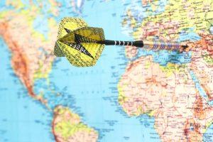 dart thrown into map denoting travel destination