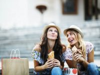 two beautiful women eating sandwiches
