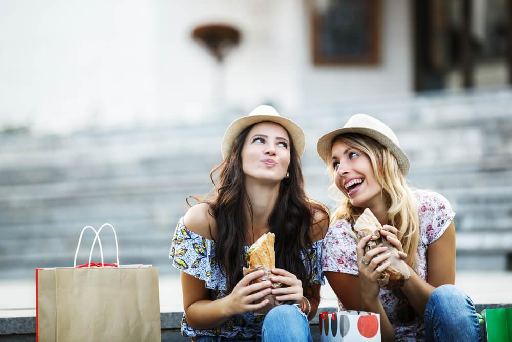 two beautiful women eating sandwiches