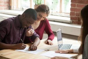 interracial couple signing lease on new home