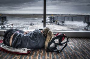 female napping on floor in airport