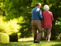 elderly couple walking in park