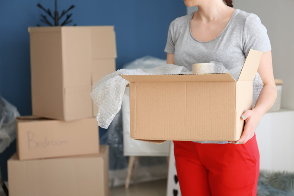 Young woman with box indoors. Moving into new house and donating excess items