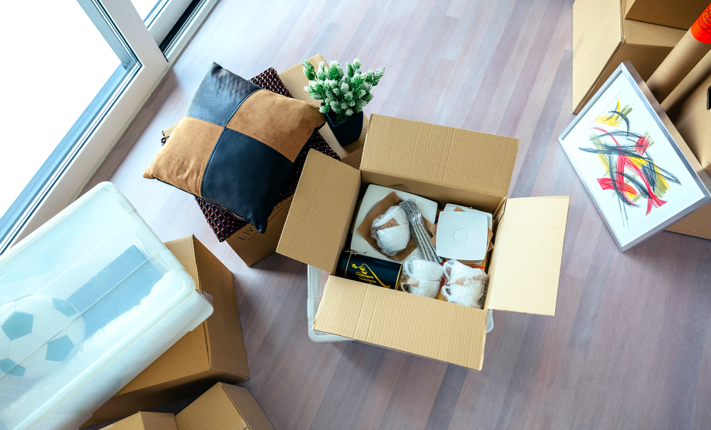 Large living room with stack of moving boxes and open kitchenware box ready to be moved to appropriate parts of home